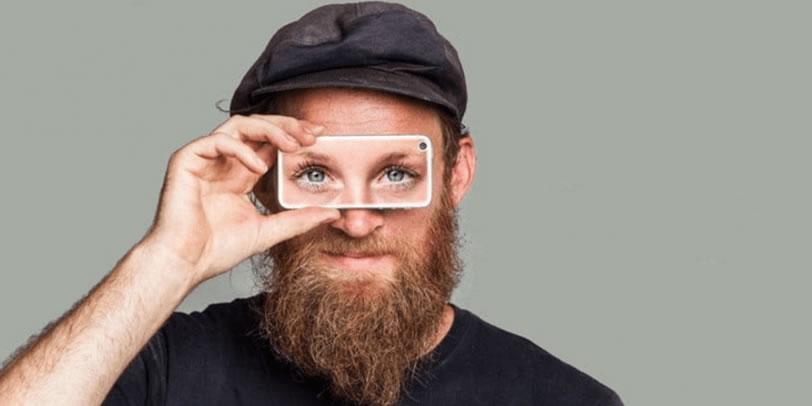 človek držiaci pred očami telefón na ktorom sú zobrazené oči