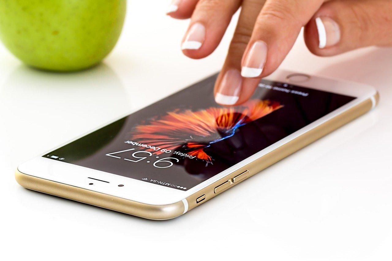 Dotykový iPhone na úvodnej obrazovke a ruka dotýkajúca sa ikony