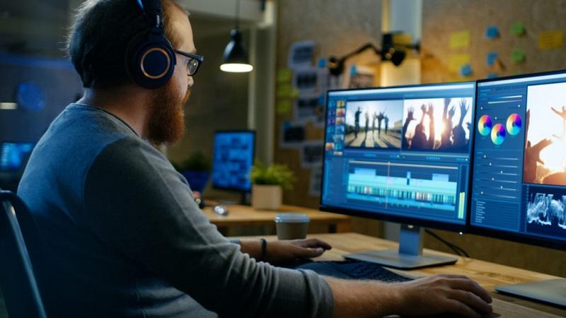 človek sedí pred počítačom so slúchadlami na ušiach